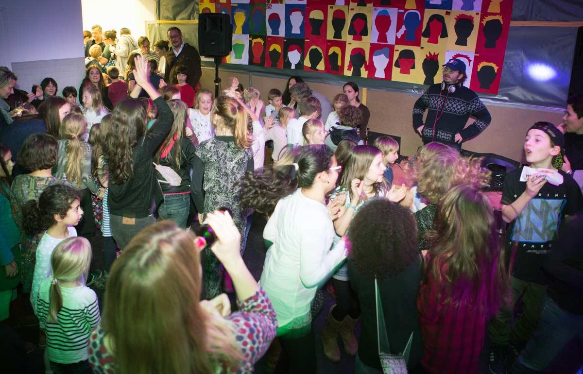 Kinder in der Aula der Platanus-Schule tanzen vor einem DJ-Pult
