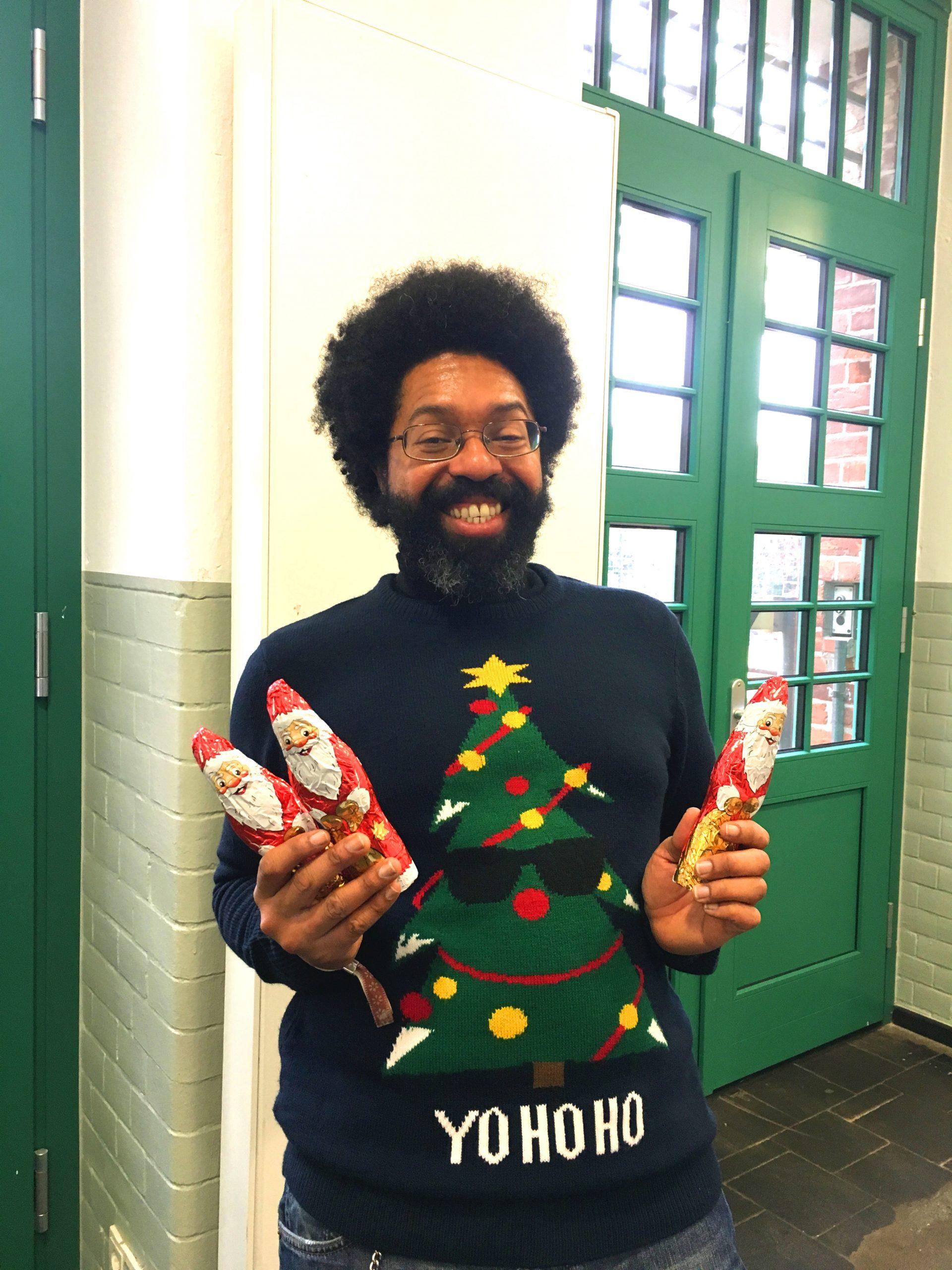 Unser Kollege Chester im Weihnachtsmannpullover, der Schokoweihnachtsmänner verteilt.
