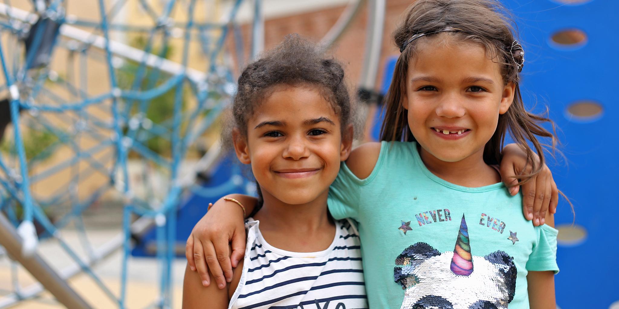 Zwei Mädchen Arm in Arm auf dem Schulfhof