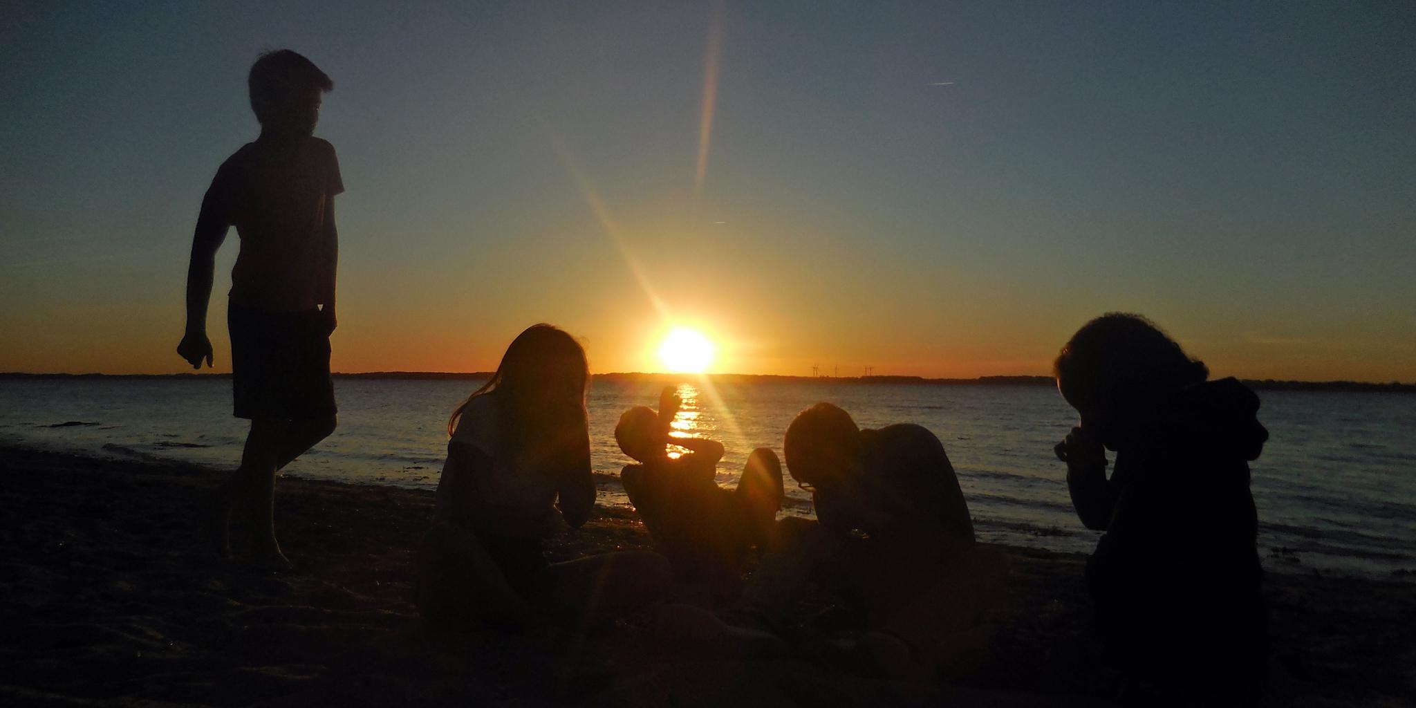 Jugendliche am Strand im Sonnenuntergang