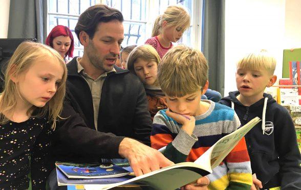 Mann liest mehreren Kindern vor.